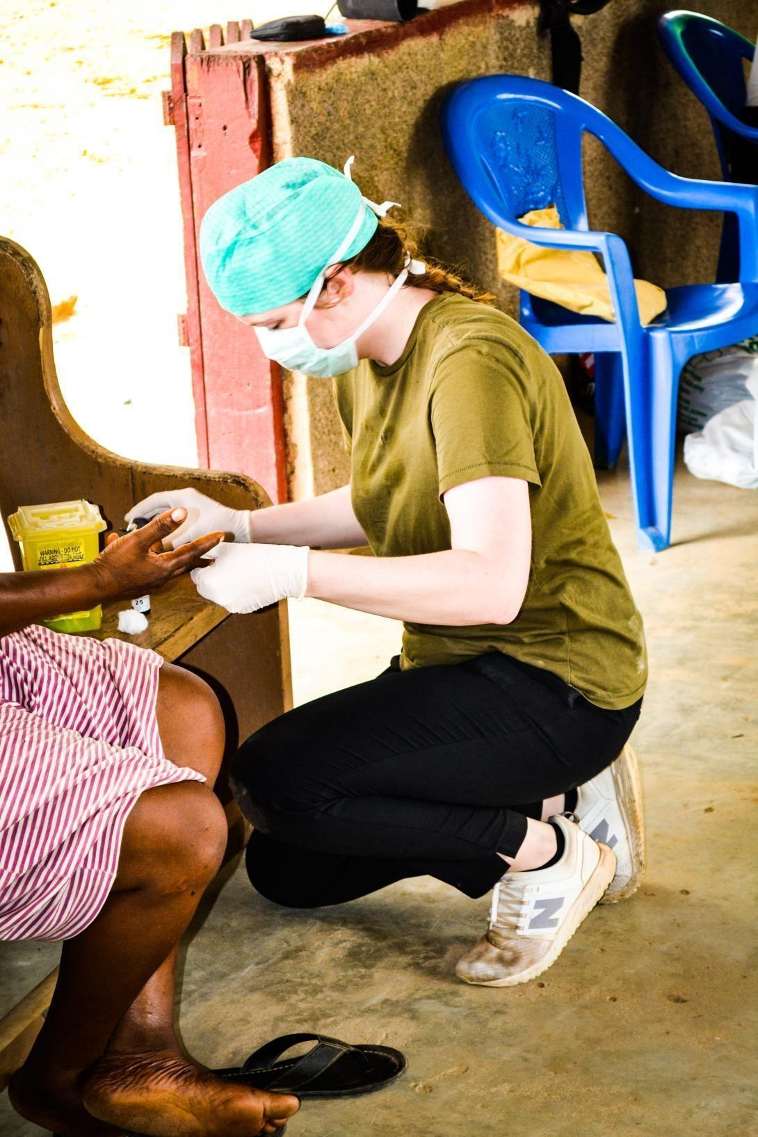 A healthcare volunteer in wearing a protective mask and gloves treats a patient on a medical internship in Ghana